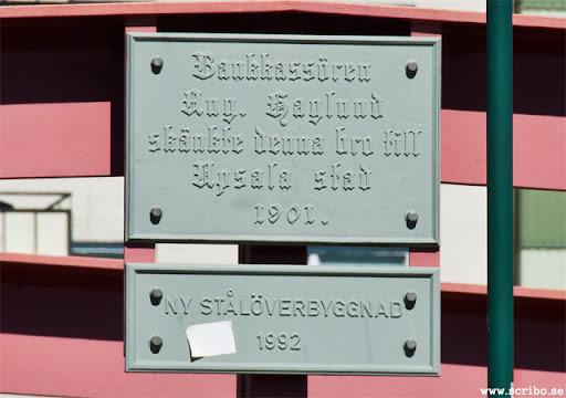 Skylt. Bankkassören Aug. Haglund skänkte denna bro till Uppsala stad 1901. Ny stålöverbyggnad 1992.
