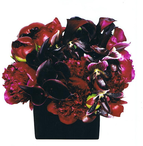 Blood red peonies, lady slipper orchids, black calla lilies, and privet berries make a lovely display.