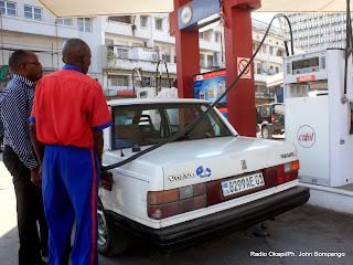 Un pompiste  (en bleu rouge),  approvisionnant un client  en carburant dans une station service à Kinshasa. Radio Okapi/Ph. John Bompengo
