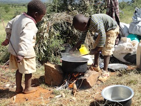 Victor Muruga (r) and his three-year-old brother Ian Kimani (l) prepare lunch from their camp at 