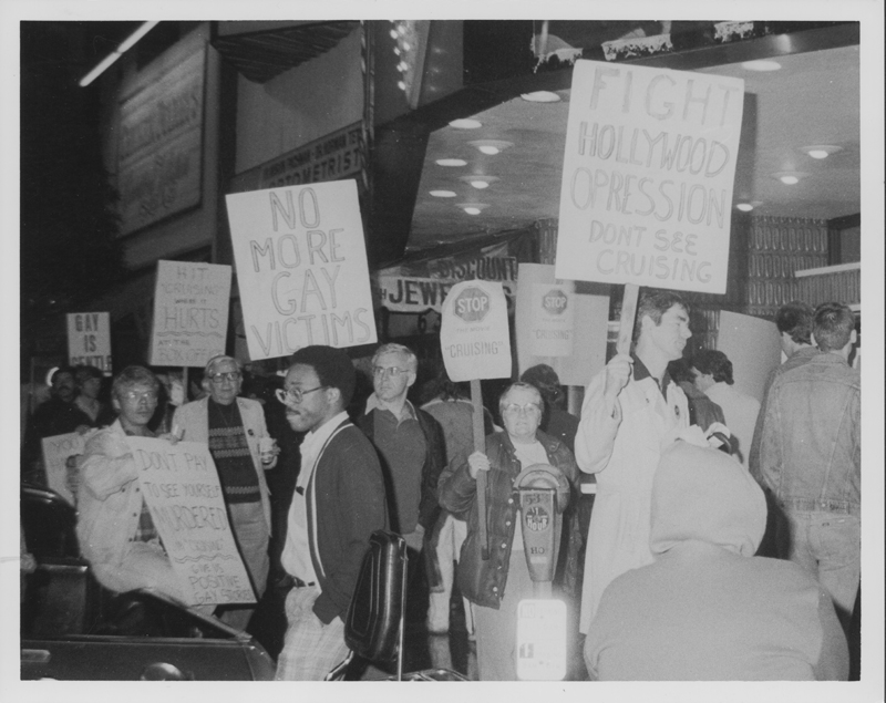 "Protesters picket the movie ""Cruising,"" including  Morris Kight (left, holding a cup) and Ivy Bottini (center, directly behind parking meter). This demostration was one of a number of protests concerning the misrepresentation of the LGBT community by Hollywood.1980."