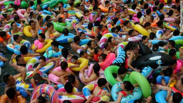 Mass crowds of people attempt to cool off at a water park in Suining, Sichuan province on Saturday, 27 July 2013 amid a record heat wave hitting 19 provinces and regions in China. People are packing into swimming pools or taking refuge in caves to escape the fierce temperatures. Local governments are resorting to cloud-seeding technology to try to bring rain to millions of acres of parched farmland. Photo: CNN