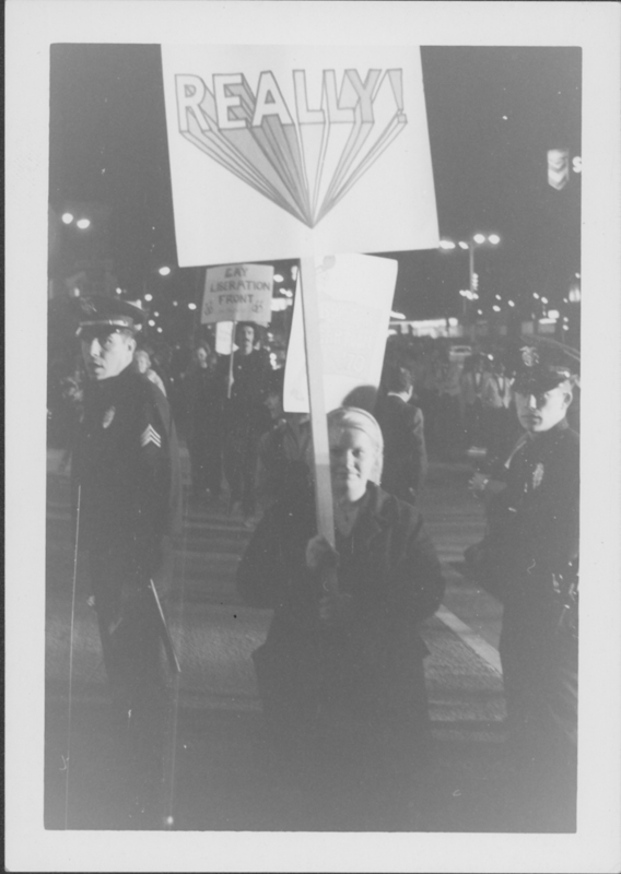 "Woman holding a sign that reads ""REALLY!"" at a protest, possibly of the movie ""Boys in the Band."" November 1969."