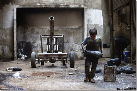 Issa, 10, carries a mortar shell in a weapons factory of the Free Syrian Army in Aleppo, September 7 - Copy