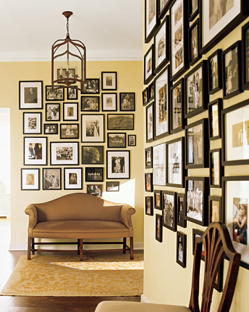 A pale yellow is the perfect backdrop for a collection of photos in black frames.