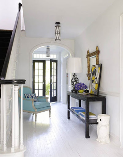 A turquoise chair gives a burst of energy to this entryway. (Jonathan Adler)