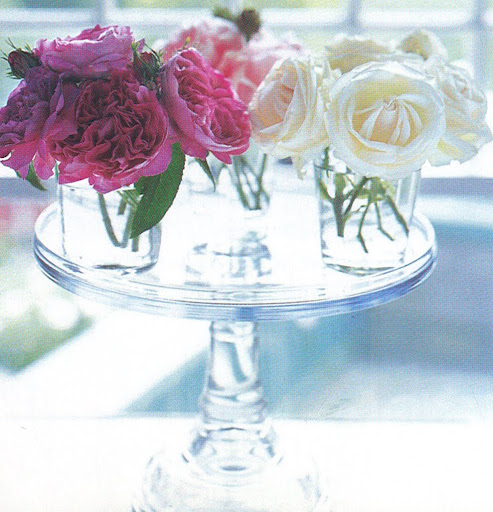Three glass tumblers filled with three colors of roses top a cake stand for a pretty, light-filled centerpiece. (The Best of Martha Stewart Living -- Arranging Flowers)