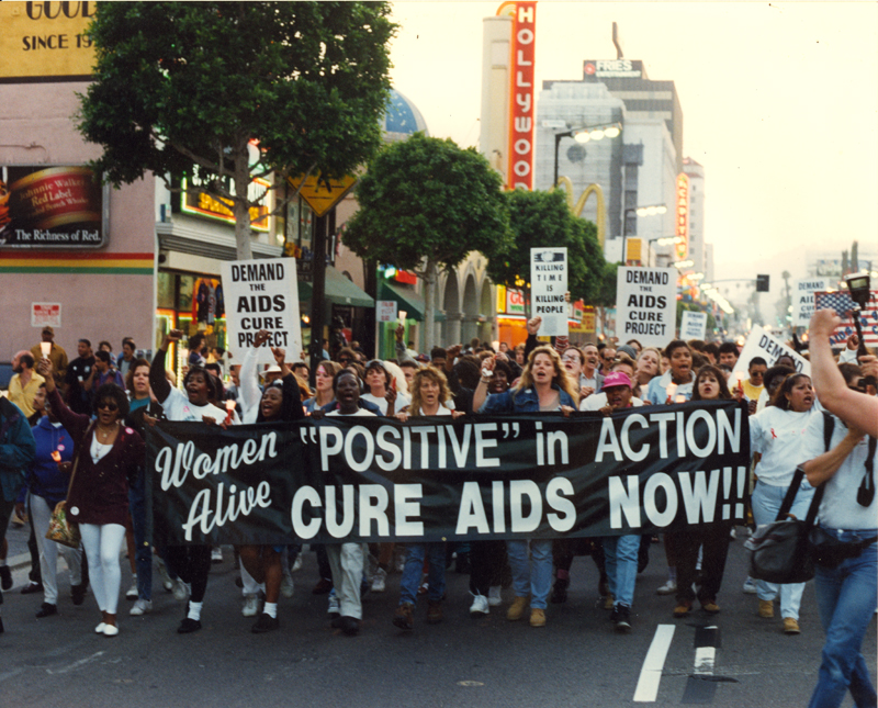 "Women Alive group carry the banner ""'Positive' in Action / Cure AIDS Now!!"" in support of the AIDS Cure Project. Circa 1994."