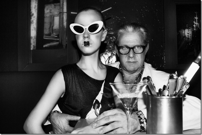 Older-man-holding-theatrically-dressed-young-woman-with-an-provocative-expression-using-a-knife-as-they-enjoy-their-nightlife-in-a-red-lounge-6069-006-NSR3866bw