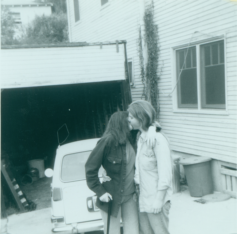 Carolyn Weathers and Denise Crippen kissing on driveway at Morton Avenue. Circa October 1975.