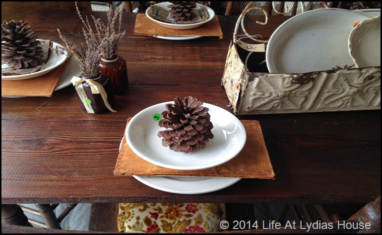 Round top table with pinecones and book backs via Life At Lydias House
