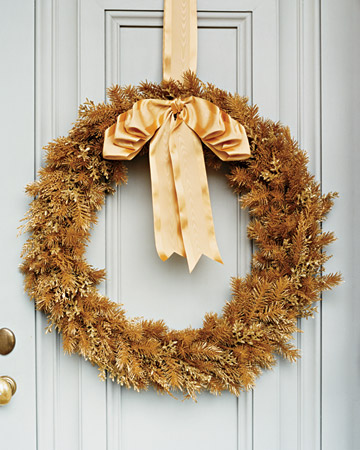 This wreath made from faux gold leaves and branches is a modern take on the traditional wreath.