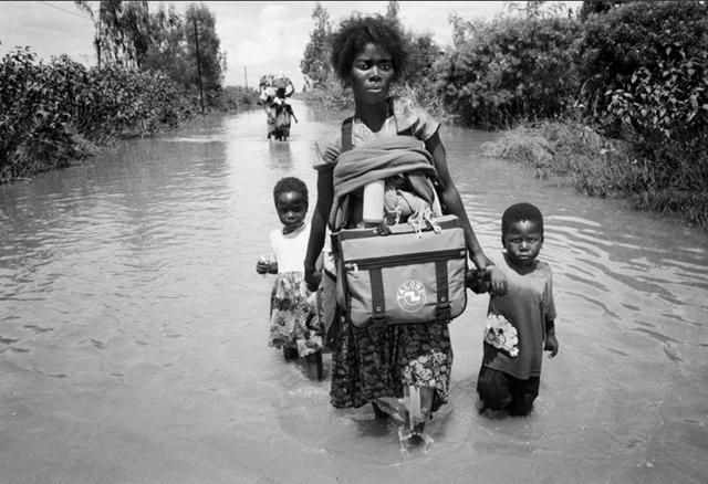A mother and her two boys walk through floodwaters in Mozambique, Africa, January 2013. Photo: Tom Stoddart / cpi-reps.com