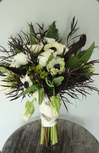 White Ranunculus, Anemone and Parrot Tulips are surrounded by feathery Agonis and Ferns with Black feather accents. blush floral design
