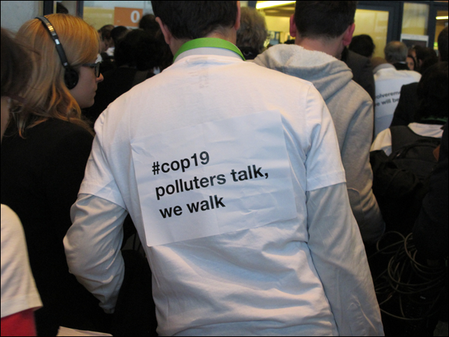 Environmental activist at the COP19 climate summit walks out, wearing a sign that reads '#cop19 polluters talk, we walk', on 21 November 2013. Photo: Brendan DeMelle / DeSmogBlog