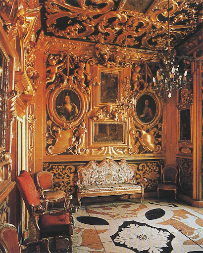 An ancient Italian fortress is richly carved and gilded, framing family portraits. Crazy beautiful.
