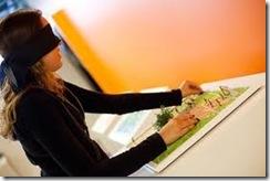 Mulher com venda nos olhos tateando uma das obras expostas