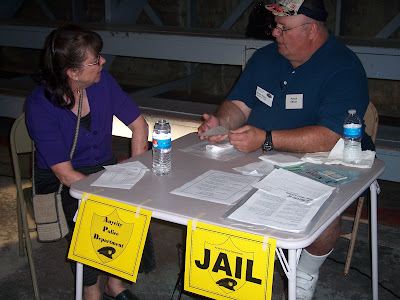 Sallie Graves (representing a person in poverty) at the simulation jail visiting with Ray Atkins (representing a police officer and illegal activities person) trying to work out a solution to her situation.  Photo courtesy of the Washington County Extension.