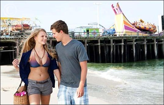 teenage_couple_walking_on_beach_is098u5j0