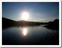 Klockan är 17:17 och solen sänker sig mot bergen.