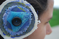 Circular hair clip stitched up with fabrics, scarf and a button.