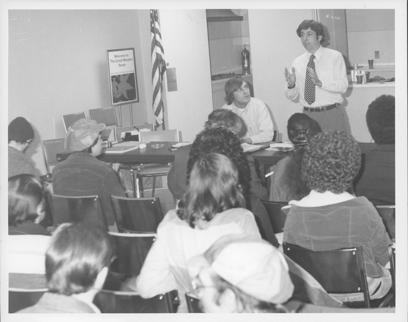 Tom Hayden speaks to the Stonewall Democratic Club with club vice-president Gerry Parker sitting next to him. 1976.