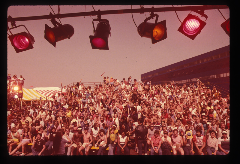 Crowd gathered before the festival stage at the Los Angeles Christopher Street West pride parade. 1982.