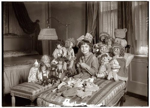It's a girl knitting with her dolls, on her bed.