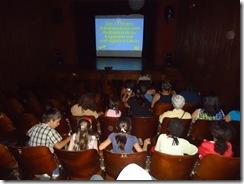 Crianças em um auditório - a frente delas um telão