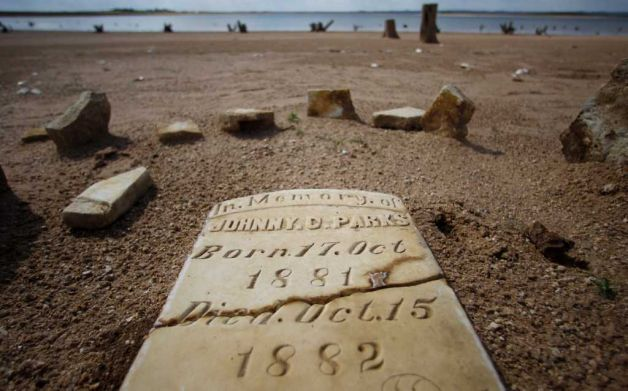 In this 5 October 2011 photo, a child's grave site, normally at least 20 to 30 feet underwater, has joined other remnants of old Bluffton, Texas, resurfacing on the now dry, sandy lake near Bluffton, as the Texas drought shrinks the state's largest inland lake. Photo: Eric Gay / AP