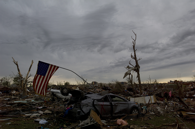 An American flag droops in the remains of a destroyed home in Moore, Oklahoma, 21 May 2013. Photo: Danny Wilcox Frazier / Redux / TIME