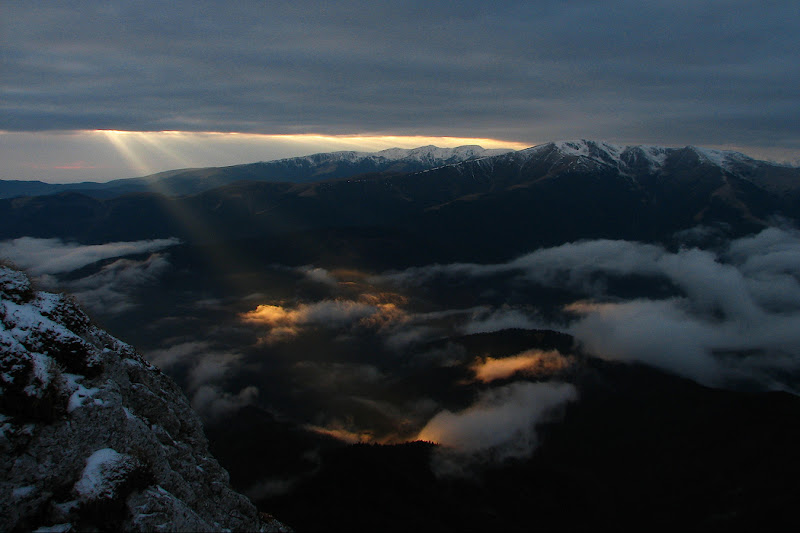 Rays of light pierce through the blanket of clouds, Piatra Craiului, Romania.