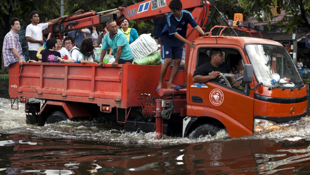 Thai residents ride on a truck through floodwaters as they evacuate their neighborhood next to the Chao Praya river in Bangkok, 28 October 2011. AFP / Getty Images