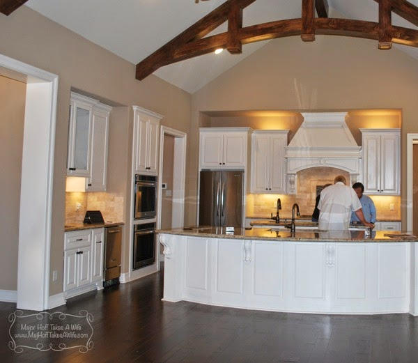 White kitchen with curved island and corbels