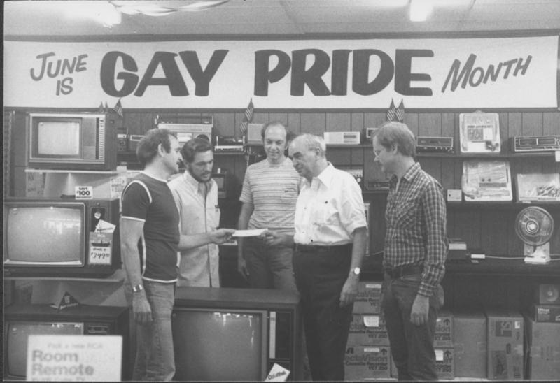 Gene Kittridge, owner of Gene's TV and long-time gay/lesbian philanthropist, contributes money to Jim Kepner (second from right) of the National Gay Archives. Standing far right is Gary Hundertmark, past archives board president. 1980.