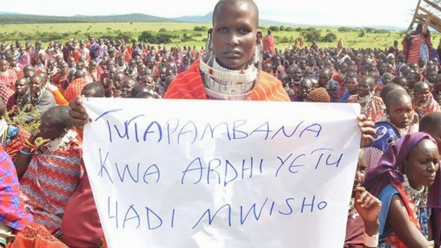 _67022111_a_maasai_woman_holds_a_sign_that_reads_in_swahili,_'we_will_fight_for_our_land_until_the_end'