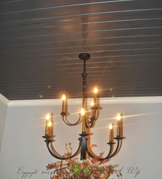 Dark grey planked ceiling with hanging traditional chandelier