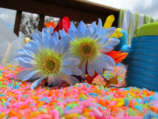 Silk flowers and watering can for gardening sensory bin with Rainbow Rice & Garden Sensory Play