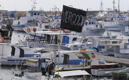 """Uno striscione nero con la scritta """"vergogna"""" al porto di Lampedusa"""