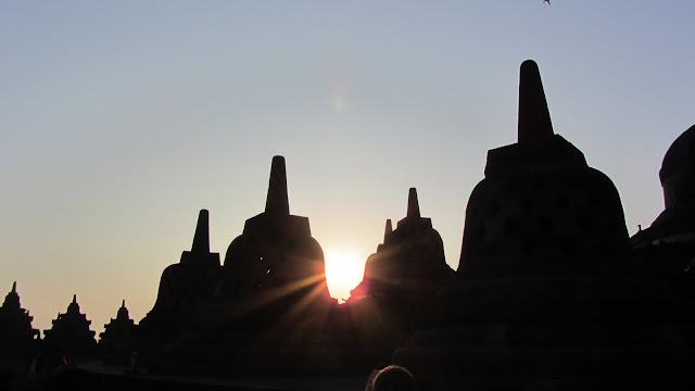 Sunrise over the circular stupas at the top of Borobudor.