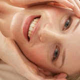 Young woman lying on bed, smiling, portrait, elevated view, close-up