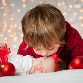 Christmas Sibling Love  by Mike DeMicco - Public Holidays Christmas ( babies, xmas, christmas, holidays, kids, siblings, bokeh, sister, lights, love, kiss, brother, decorations )
