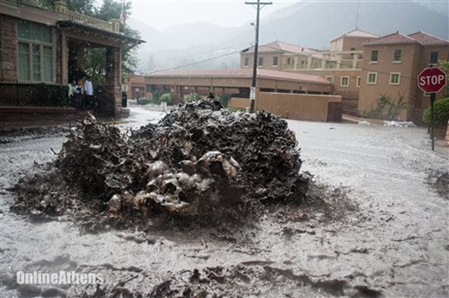 Flood water shoots out of a sewer on Canon Avenue on Thursday, 12 September 2013, in Manitou Springs, Colorado. Flash flooding in Colorado has cut off access to towns, closed the University of Colorado in Boulder and left at least three people dead. Photo: Michael Ciaglo / The Colorado Springs Gazette