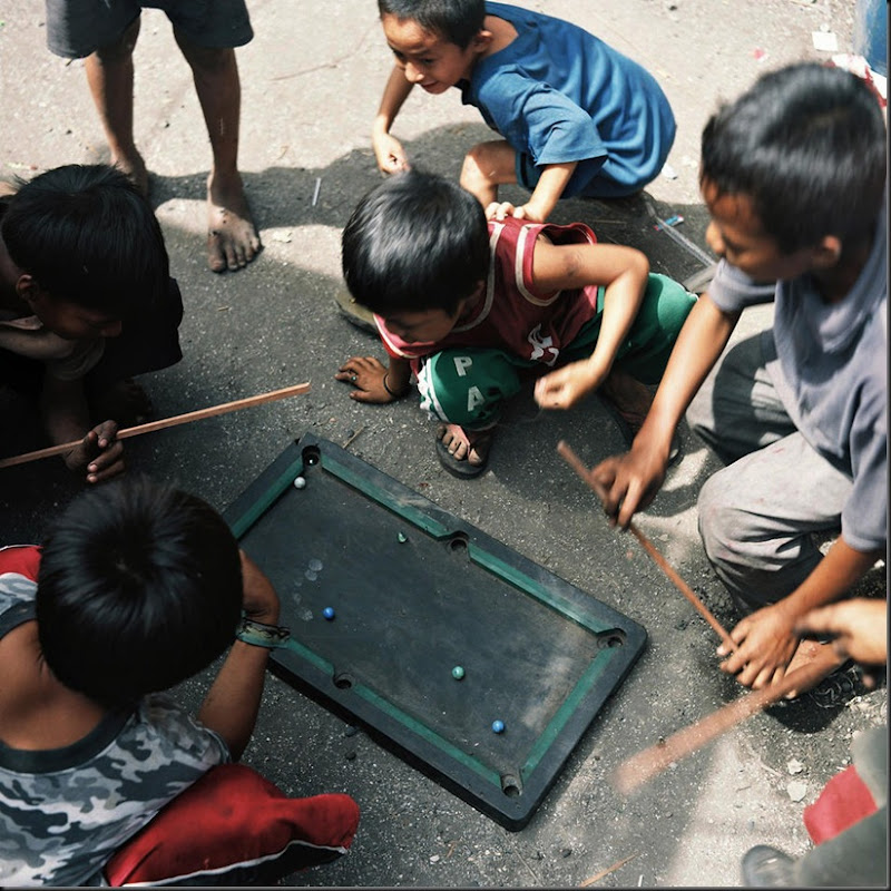 "Children of residents of Happyland play on a makeshift billiards table. Happyland is a large garbage dump in Manila where families of scavengers and charcoal-makers call the place home. The place and its adjacent poverty-stricken areas are also fondly called ""children factory"" due to the sheer number of children and pregnant women living in the community."