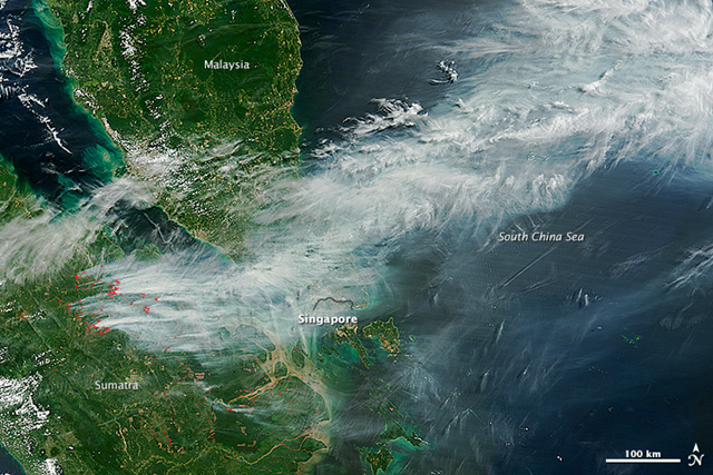 On the morning of 19 June 2013, NASA's Terra and Aqua satellites captured this striking image of smoke billowing from illegal wildfires on the Indonesian island of Sumatra. The smoke blew east toward southern Malaysia and Singapore, and news media reported that thick clouds of haze had descended on Singapore, pushing pollution to record levels. Farmers in Sumatra often burn forests during the dry season to prepare soil for new crops. Photo: Jeff Schmaltz / NASA