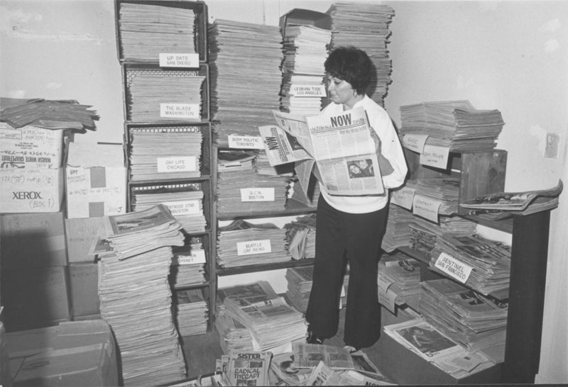 Lesbian activist Joy Commander at the National Gay Archives looking through the newspaper collection. 1980.