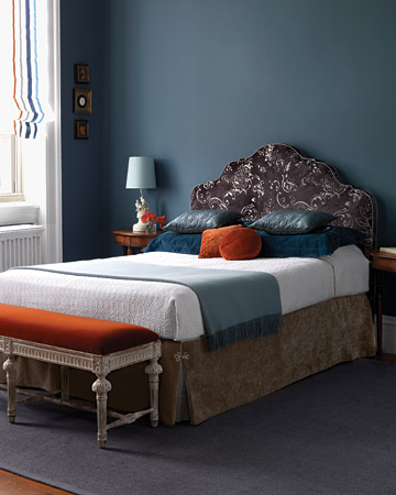 Orange looks great with blue. The bedroom in this picture is cool and sophisticated. The orange ribbon trim on the roman shade as well as the orange velvet pillows and bench upholstery keep the room from appearing gloomy and unfriendly.