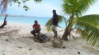Ein Lomo (Erdofen) wird vorbereitet. In einer Grube wird ein Lagerfeuer gebaut, darauf werden Steine geschichtet.