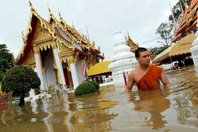 A Buddhist monk wades through waist-deep flood water near a temple in Thailand, 8 October 2011. abc.net.au