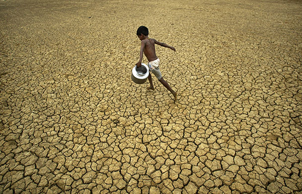 Berhampur, India: A village boy runs through a parched field on World Water Day 2010. Photo: Biswaranjan Rout / AP